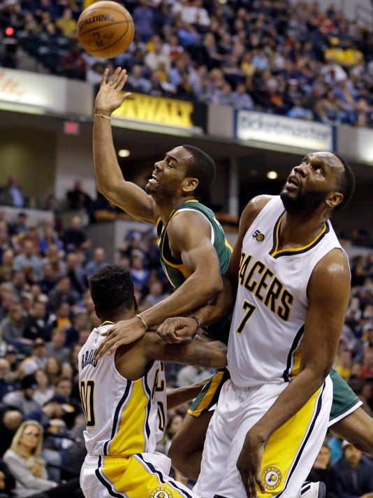 Utah Jazz guard Alec Burks (10) is fouled by Indiana Pacers guard Aaron Brooks (00) and center Al Jefferson (7) during the second half of an NBA basketball game in Indianapolis, Monday, March 20, 2017. The Pacers defeated the Jazz 107-100. (AP Photo/Michael Conroy)