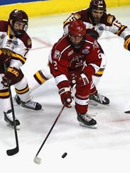 Harvard's Tyler Moy  moves the puck between Adam Johnson (left) and Willie Raskob of Minnesota-Duluth during their NCAA semifinal matchup April 6, 2017, at the United Center n Chicago.