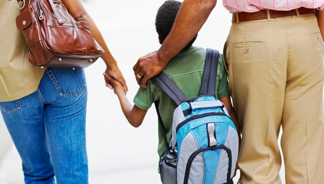 Parents walking their son to school.