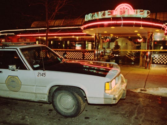 A police cruiser sits parked in front of Drake Diner, where employees Tim Burnett, 28, and Cara McGrane, 25, were shot and killed on Nov. 29, 1992.