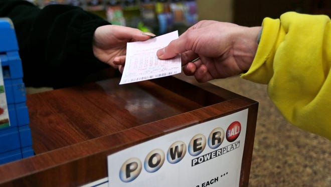 A clerk hands a ticket with five computer quick picks to a customer for Wednesday's Powerball jackpot at the Mobil Mart in Methuen, Mass., Tuesday, Jan. 12, 2016. (AP Photo/Charles Krupa)