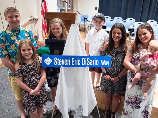 Eric DiSario's family stand with the street sign dedicated