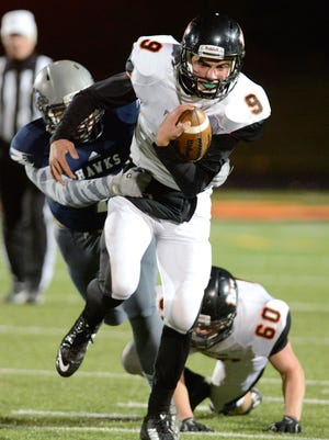 West De Pere quarterback Beau Mommaerts shakes off Appleton Xavier linebacker Drew Hinkens in the first half at West De Pere High School in De Pere, Wis. on Friday, Oct. 31, 2014.