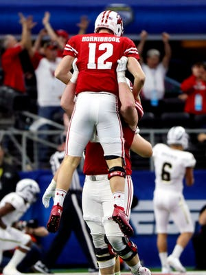 Badgers quarterback Alex Hornibrook celebrates with offensive lineman Beau Benzschawel after throwing a touchdown pass against Western Michigan in the Cotton Bowl last season.