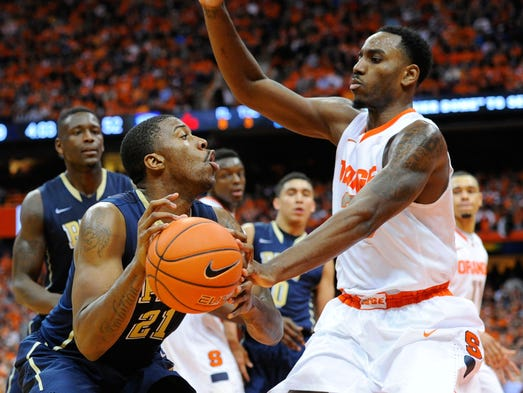 Syracuse forward Rakeem Christmas, right, attempts to knock the ball out of the hands of Pittsburgh forward Lamar Patterson during the second half at the Carrier Dome.  Syracuse defeated Pittsburgh, 59-54.