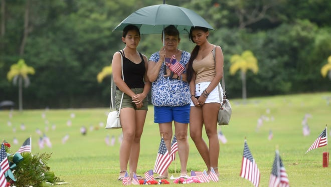 Christina Alvarez, center, with her granddaughters Chloe Alvarez, left, 15, and Janesia Alvarez, 14, visits the gravesite of her father Jose S. Pangelinan, a Vietnam veteran, and mother Lydia G. Pangelinan, on Memorial Day at the Guam Veterans Cemetery, May 28, 2018.