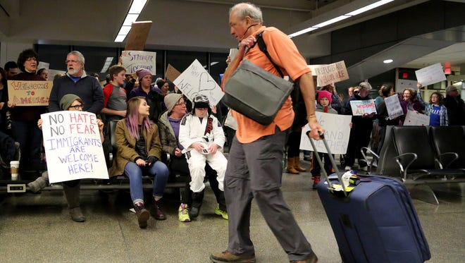 Travelers arriving to at the international gate of the Minneapolis-St. Paul International Airport are greeted by protesters demonstrating against an executive order signed by President Donald Trump, restricting immigration from several Muslim nations Saturday, Jan. 28, in Minneapolis.
