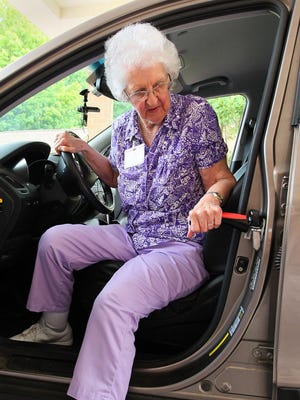Vi Bahm exits a car using the Car Cane. It claims you can get in and out of your car with ease.