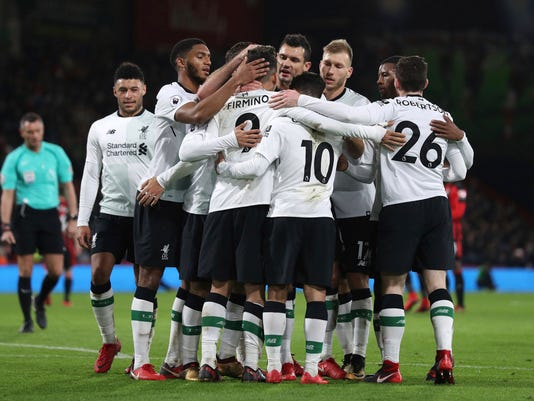 Liverpool's Roberto Firmino, center, is mobbed by his team-mates after scoring his side's fourth goal during the English Premier League soccer match at the Vitality Stadium in Bournemouth, England, Sunday Dec. 17, 2017. (Andrew Matthews/PA via AP)