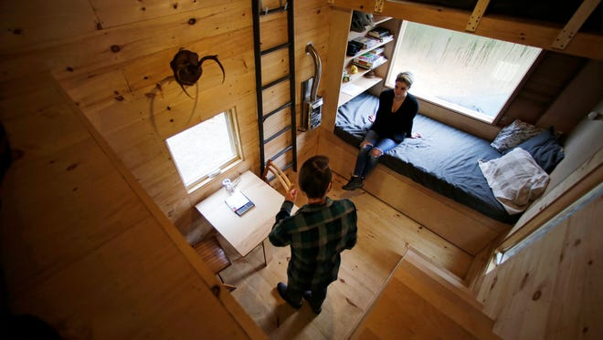 Shane Lentz of Pittsburgh and his wife, Hilary, talk before leaving a tiny house, which they rented for a weekend, in Croydon, New Hampshire, in 2015. A conference about tiny house living is set for April 2-3 in Asheville.