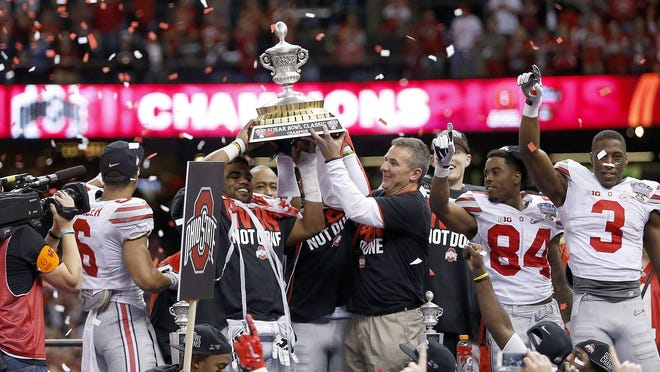 Coach Urban Meyer and running back Ezekiel Elliott hold up the trophy following a College Football Playoff semifinal win over Alabama in the Sugar Bowl in New Orleans on Jan. 1, 2015. Not every Ohio State season ends in a title, but they rarely end with losing records. Not since 1922-24 have the Buckeyes had consecutive losing seasons.