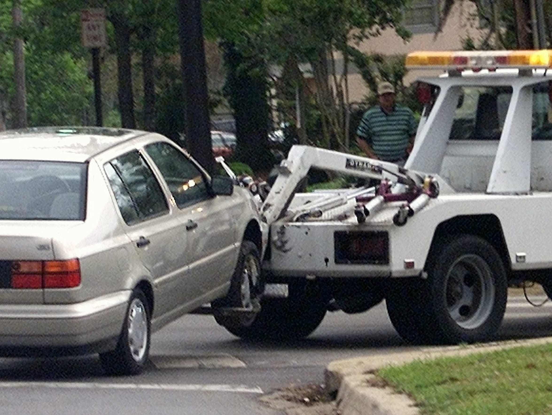 A car is towed away from an FSU parking lot by a DeLoach