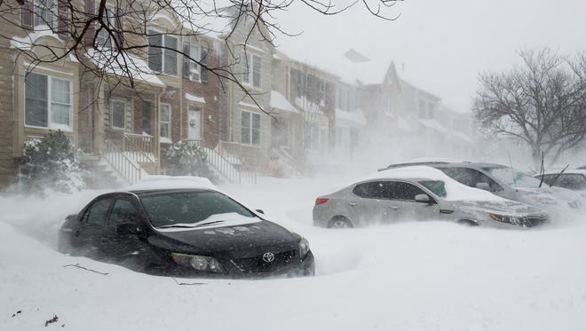 Blowing snow forms drifts around parked cars, January 23, 2016 in Prince William County, Virginia.