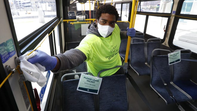 Robert Day works on disinfecting surfaces on a bus in Detroit, Wednesday, April 8, 2020. West Michigan Express, a planned coach bus line connecting Grand Rapids and Holland, has effectively shuttered its planning due to the coronavirus pandemic.