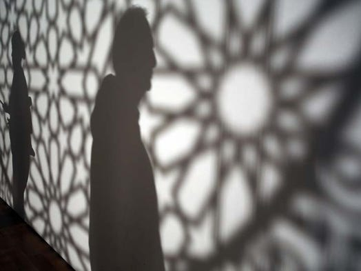 "Silhouettes are people taking in the 3-D piece of Anila Quayyum Agha's ""Intersections"" at the Grand Rapids Art Museum Tuesday, Sept. 30, 2014 during artprize 2014."