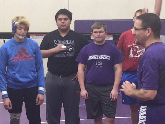 Kiana Pugh (blue sweatshirt) listens to Mosinee wrestling