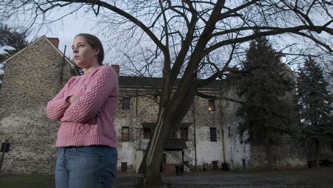 """Marisa Bozarth,a museum attendent at the Burlington County Prison Museum in Mount Holly stands in the museum's prison yard.  The Sci-Fi channel's """"Ghost Hunters"""" filmed there recently because of speculation that the museum may be haunted."""