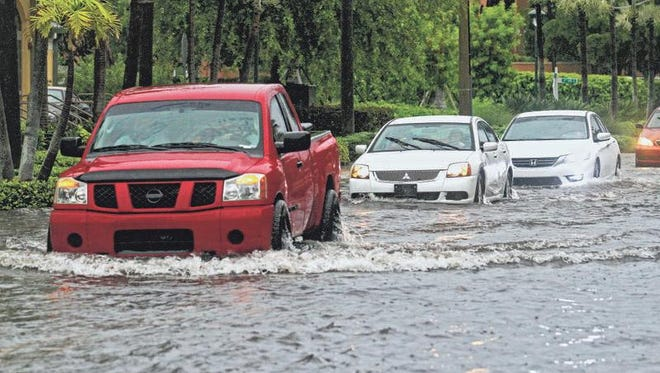 Motorists navigate their way through severe flooding on 10th Avenue South in Naples on Monday. The city received 6.5 inches of rain.