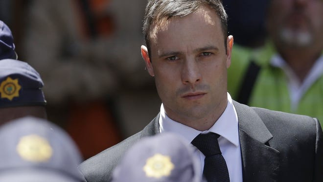 Oscar Pistorius leaves court surrounded by police on Friday, Oct. 17, 2014, in Pretoria, South Africa. He received a five-year prison term after being convicted of culpable homicide — instead of murder — in his girlfriend's shooting death.
