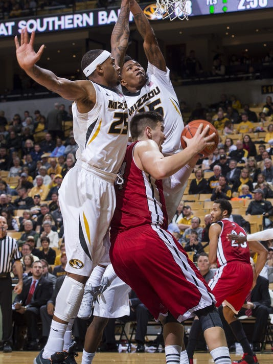 Northern Illinois's Marin Maric, bottom, tries to shoot past Missouri's Russell Woods, left, and Wes Clark during the second half of an NCAA college basketball game Friday, Dec. 4, 2015, in Columbia, Mo. Missouri won the game 78-71. (AP Photo/L.G. Patterson)