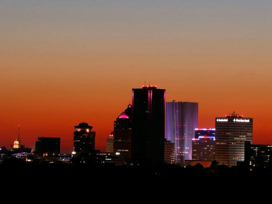 The sun sets behind the skyline in downtown Rochester,