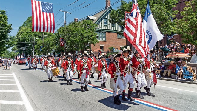 Marchers follow the red, white and blue stripes painted in the center of town during the Bristol Fourth of July Parade in 2016.
