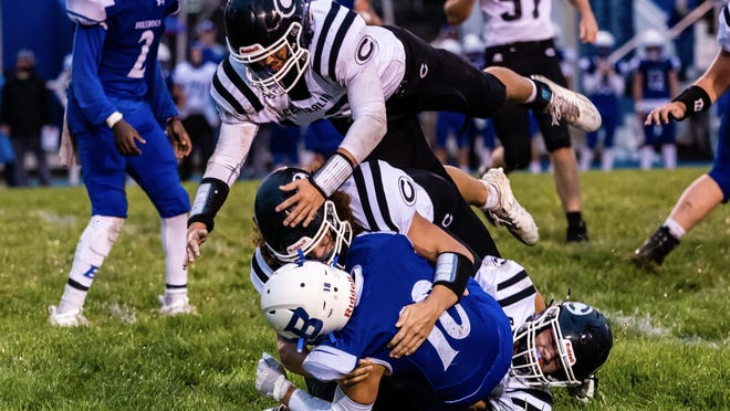 Centralia players team together to make a tackle against Brookfield during a game Friday night in Brookfield.