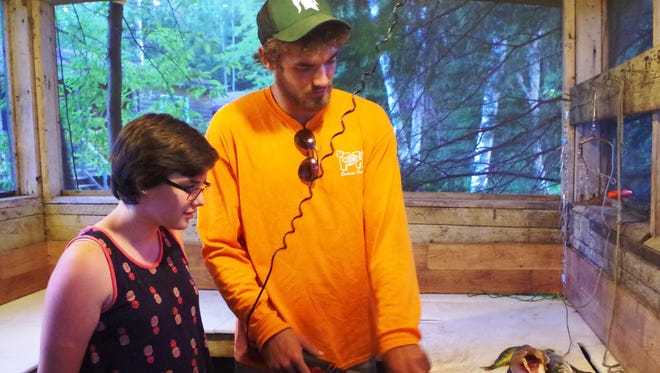 Wolfgang Lohrer, 19, teaches his youngest sister, 11-year-old Nina, to clean fish at PK Resort in northern Ontario.