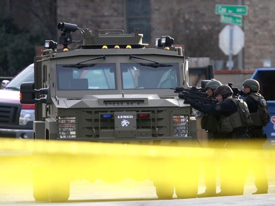 Officers take cover behind a vehicle during a standoff