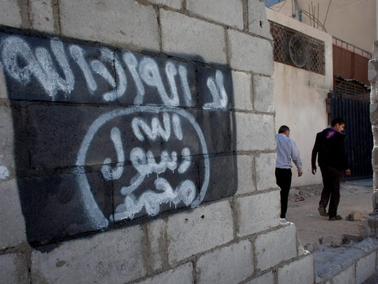 Men walk past graffiti depicting the flag of the Islamic