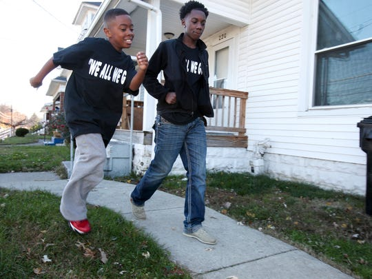 Ki'Anthony Tyus, 10, left, and Diontae Reed, 14, head to the next home in the Shawnee neighborhood as they hand out information about the Hood 2 Hood campaign to end violence in the community.