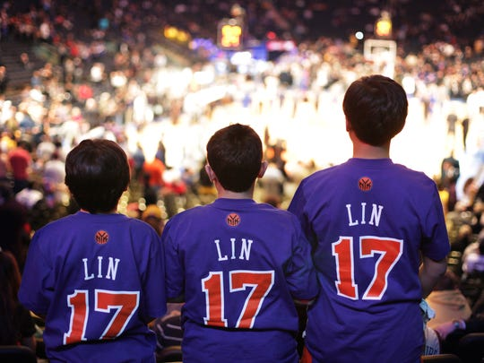 Fans of Knicks PG Jeremy Lin  watch a game against