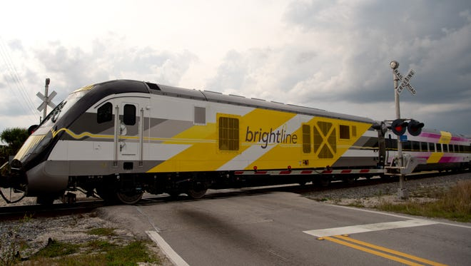 A line of Brightline passenger trains, pulled by a Florida East Coast engine, moves south past the Walton Road crossing Monday, March 13, 2017, in Port St. Lucie.