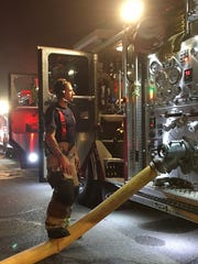 A firefighter runs the engine supplying water to the