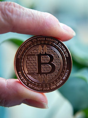 This May 1, 2014 photo taken in Washington, DC shows a bitcoin medal. Bitcoin uses peer-to-peer technology to operate with no central authority or banks; managing transactions and the issuing of bitcoins is carried out collectively by the network. AFP PHOTO / Karen BLEIERKAREN BLEIER/AFP/Getty Images