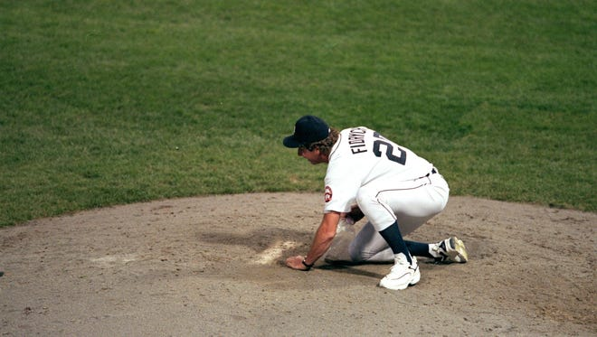 Mark Fidrych of the Detroit Tigers scoops up dirt after the last game played at Tiger Stadium against the Kansas City Royals in 1999. The Tigers defeated the Royals 8-2.