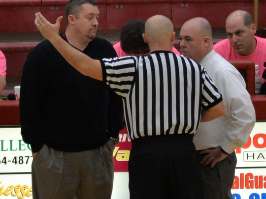 A referee talks to Riverdale coach Cory Barrett, left, and Smyrna coach Shawn Middleton during the Lady Bulldogs' win over Riverdale in a consolation game Feb. 21.