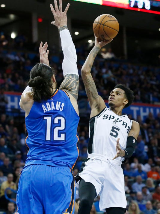 San Antonio Spurs guard Dejounte Murray (5) shoots as Oklahoma City Thunder center Steven Adams (12) defends in the first half half of an NBA basketball game in Oklahoma City, Saturday, March 10, 2018. (AP Photo/Sue Ogrocki)