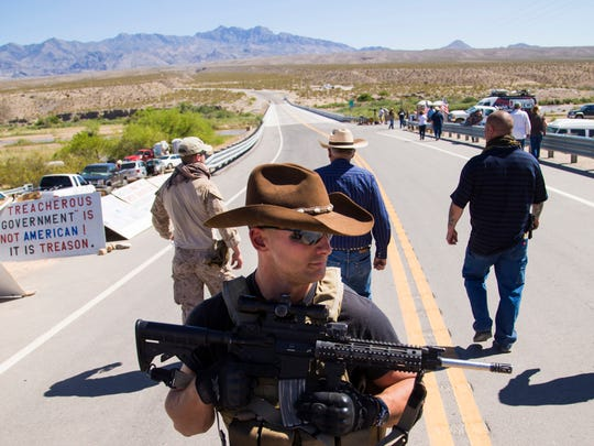 Cliven Bundy (center rear) walks away from a news conference under militia security in Bunkerville, Nevada, on April 14, 2014.