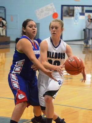 Smith Valley sophomore Mattie Johns tries to pass off against the pressure of a McDermitt defender while driving towards the basket in last Saturday's 43-34 SVHS victory.