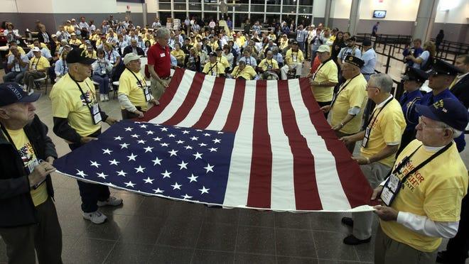 World War II and Korean veterans prepare to fold a flag at the Cincinnati/Northern Kentucky International Airport before boarding an Honor Flight in 2012.