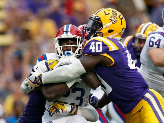 FILE - In this Sept. 22, 2018, file photo, LSU linebacker Devin White (40) tackles Louisiana Tech running back Jaqwis Dancy (23) in the first half of an NCAA college football game, in Baton Rouge, La. White is a possible pick in the 2019 NFL Draft.  (AP Photo/Tyler Kaufman, File)