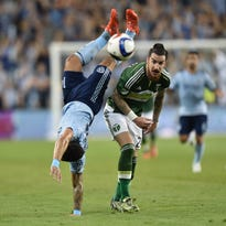 Mar 21, 2015; Kansas City, KS, USA; Sporting KC forward Dominic Dwyer (14) gets fouled as he flips over Portland Timbers defender Liam Ridgewell (24) during the first half at Sporting Park. Mandatory Credit: Peter G. Aiken-USA TODAY Sports