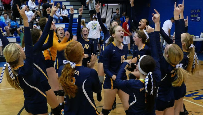 The Gulf Breeze Dolphins celebrate their volleyball victory over the Washington Wildcats Thursday evening at Washington High.  The Dolphins won their District 1-6A match in four games.