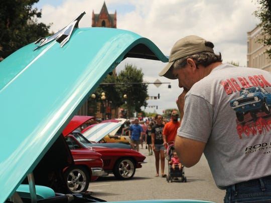 Tony Locke, who owns a 1973 Barracuda, looks at another car at the Day B-4 Father's Day Car Show in downtown Anderson.
