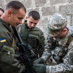 Sgt. Richard Lacombe shows Ukrainian National Guard Soldiers the proper procedures for operating an M4 rifle
