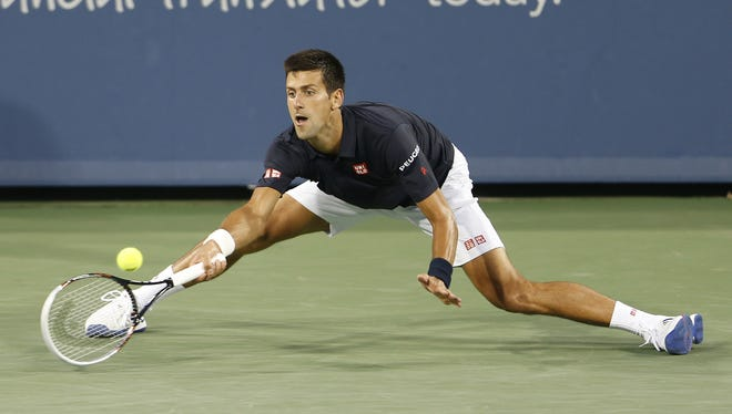 Novak Djokovic (SRB) reaches for a shot against Gilles Simon (FRA) during their first round match in the Western & Southern Open held at the Lindner Family Tennis Center in Mason, Ohio  Tuesday.