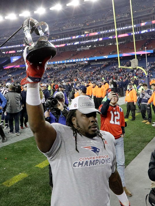 New England Patriots defensive lineman Ricky Jean Francois walks off the field with the trophy after the AFC championship NFL football game against the Jacksonville Jaguars, Sunday, Jan. 21, 2018, in Foxborough, Mass. The Patriots won 24-20. (AP Photo/Steven Senne)