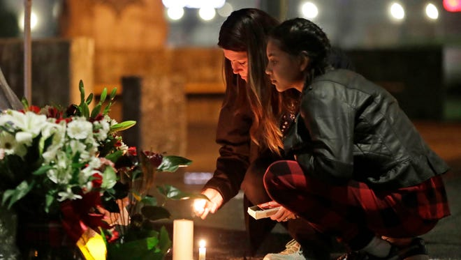Tonya Gervacio, left, and her daughter Gracie, 11, light candles Monday night at a memorial to slain Pierce County Sheriff's Deputy Daniel McCartney.