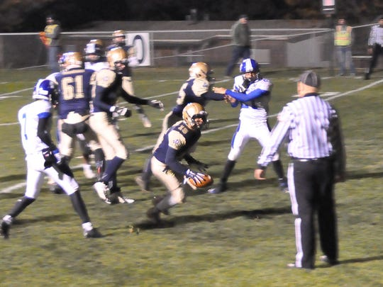 Isaiah Otero makes one of his three touchdown runs for the Ruidoso Warriors against Saint Michael's Nov.6.